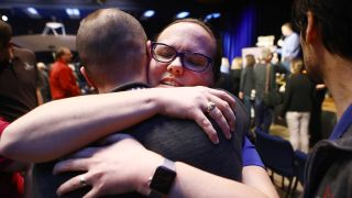 Keri Bean (facing camera), the NASA tactical uplink lead for Opportunity, hugs a colleague during a press conference discussing the end of the Opportunity mission on Feb. 13, 2019. The event took place at NASA's Jet Propulsion Laboratory in Pasadena, Calif.