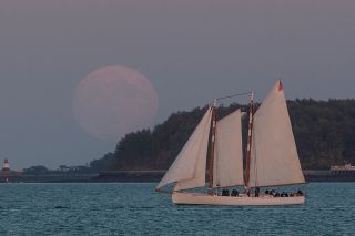 The supermoon rises over a sailboat in Boston Harbor on Sept. 27, 2015.
