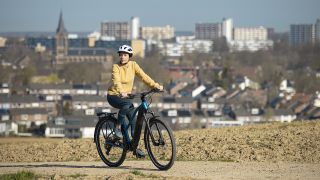 Woman riding a Shimano ebike on a trail overlooking a city