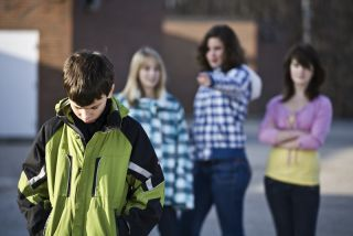 Three female bullies taunt a passing male student.