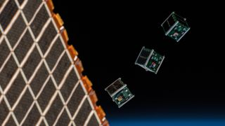 Image of three cubesats being released from the International Space Station
