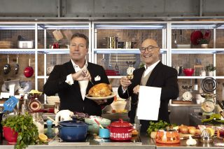 Posed shot of John Torode and Gregg Wallace surrounded by delicious food