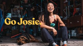 Go Josie film image, shows Josie Fouts laughing while sitting next to a dog