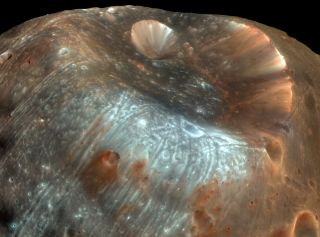 The massive Stickney Crater is the largest feature on the surface of Phobos. It stretches almost 6 miles (9.5 kilometers) at one end of the elongated moon, giving it the shape of a partially-deflated football. This color-enhanced photo was taken by the High Resolution Imaging Science Experiment (HiRISE) on NASA's Mars Reconaissance Orbiter