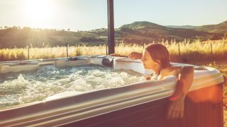 A woman relaxing in a hot tub at sunset