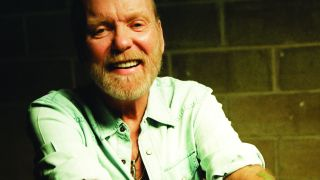 Gregg Allman in a pale green shirt looking at the camera and smiling.