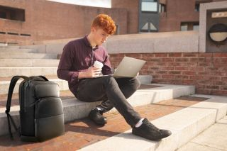 Student sitting on steps with coffee and Dell Laptop