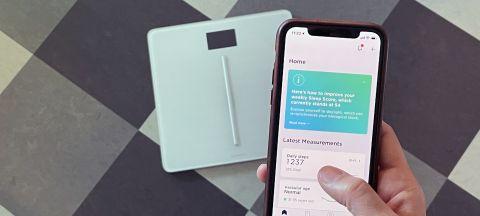 Withings Body Cardio med en telefon i förgrunden med Withings Health Mate-appen.