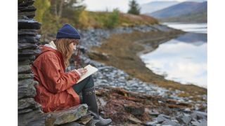 Woman nature journaling by water