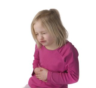 A little girl holds her stomach in pain.