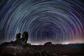 A long-exposure image shows stars appearing to whirl around Polaris, the north star, which appears fixed in the sky.
