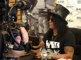 Slash signing memorabilia for fans at GuitarGuitar in Epsom