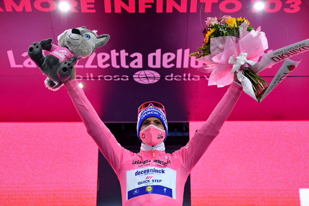 CESENATICO ITALY OCTOBER 15 Podium Joao Almeida of Portugal and Team Deceuninck QuickStep Pink Leader Jersey Celebration Flowers Mascot Mask Covid safety measures during the 103rd Giro dItalia 2020 Stage Twelve a 204km stage from Cesenatico to Cesenatico girodiitalia Giro on October 15 2020 in Cesenatico Italy Photo by Stuart FranklinGetty Images