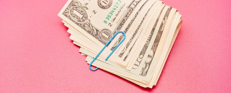 Directly above shot of a bundle of American Dollar bank notes with blue paper clip on pink background