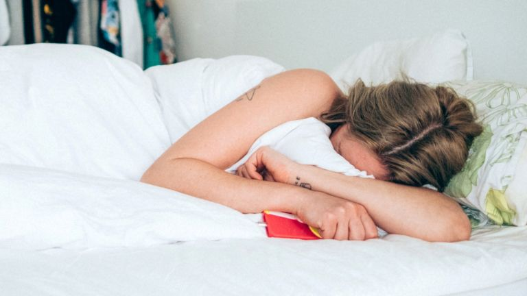 Young woman in bed, hiding her face into the duvet