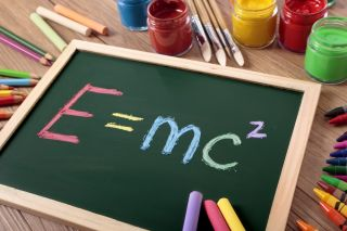 E=MC2 Einstein's famous physics formula written on blackboard.
