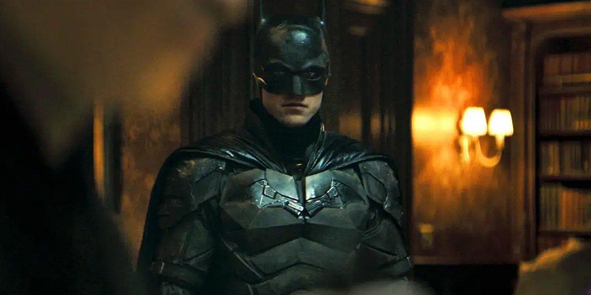 Batman (Robert Pattinson) stands at a crime scene in The Batman (2022)