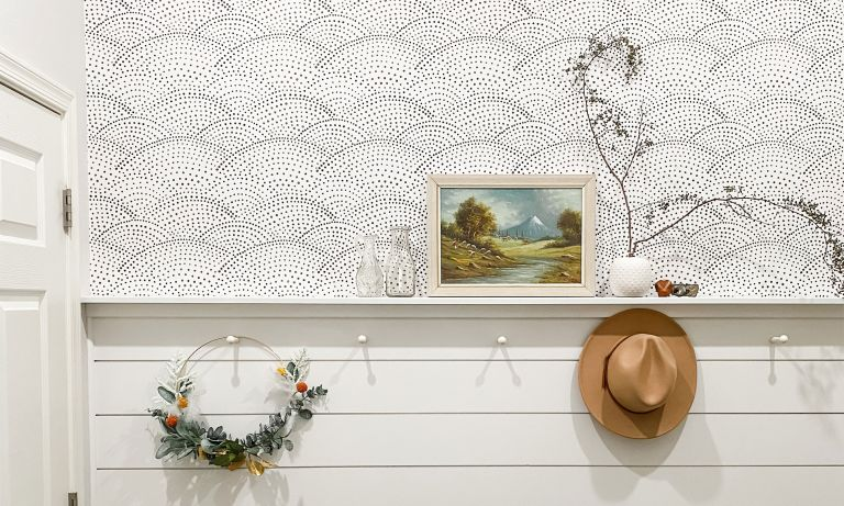 half wallpapered wall and half white shiplap with pegs and decorative foliage on shelf