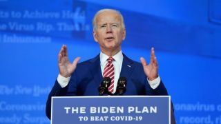 """Biden stands at a podium with a sign on it that reads """"The Biden Plan to Beat COVID-19"""""""