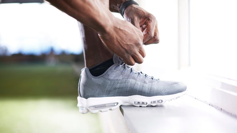 A man lacing up a pair of the best running shoes for men