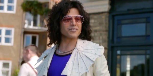 "Rami Malek as Freddie Mercury being called an ""angry lizard"" at meeting with manager John Reid in Bo"