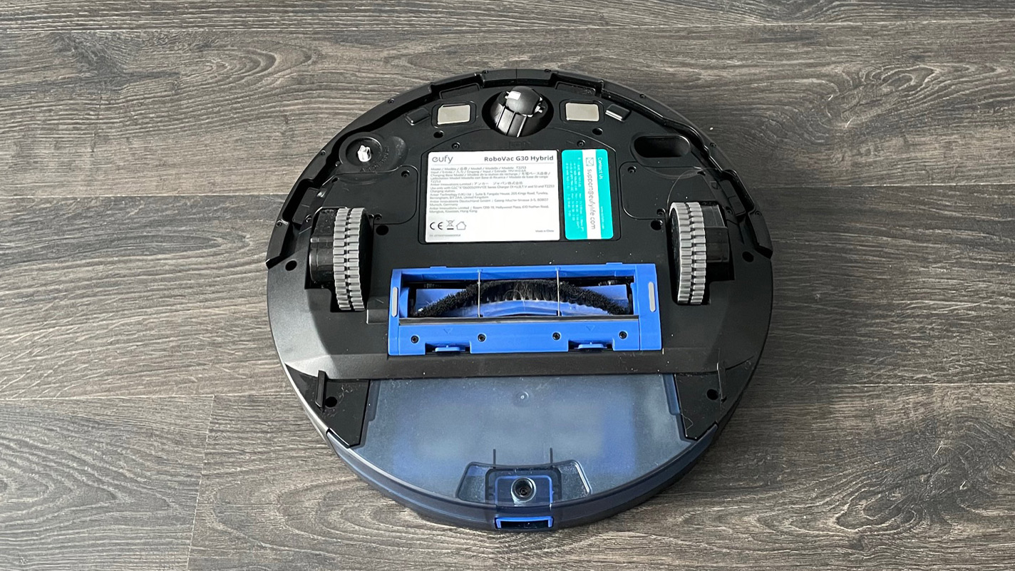 Eufy RoboVac G30 Hybrid upside down on a wooden floor without the mopping pad attached