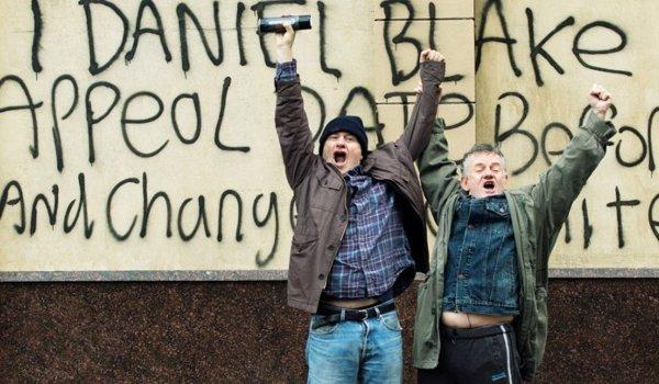 I, Daniel Blake two men standing triumphantly in front of graffiti