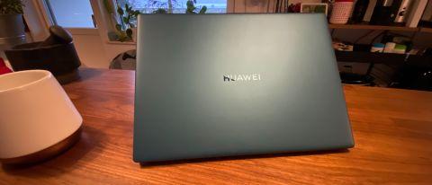 Huawei MateBook X (2020) i den skogsgröna färgen på ett bord jämte en kaffekopp.