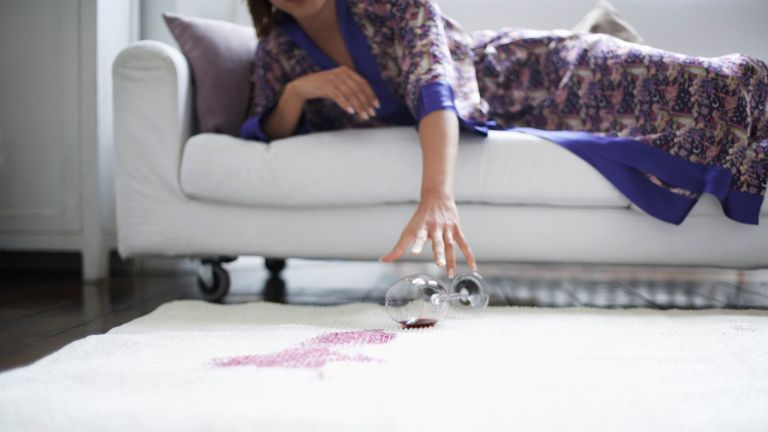 How to remove wine stains, Woman Reaching for Fallen Wine Glass