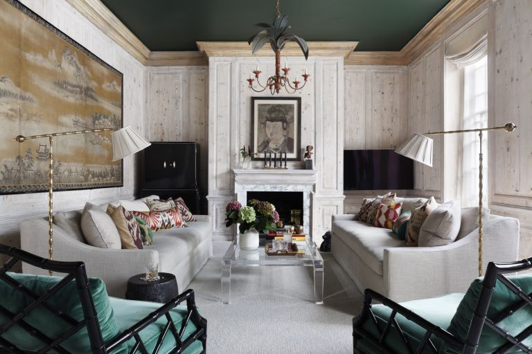 white and green living room with pleated floor lamps and botanical chandelier pendant by Studio Duggan