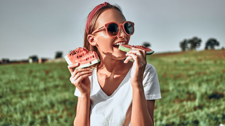 Sexy girl in red sunglasses holds a cut watermelon in her hands. Happy woman in trendy red sunglasses eat watermelon on nature