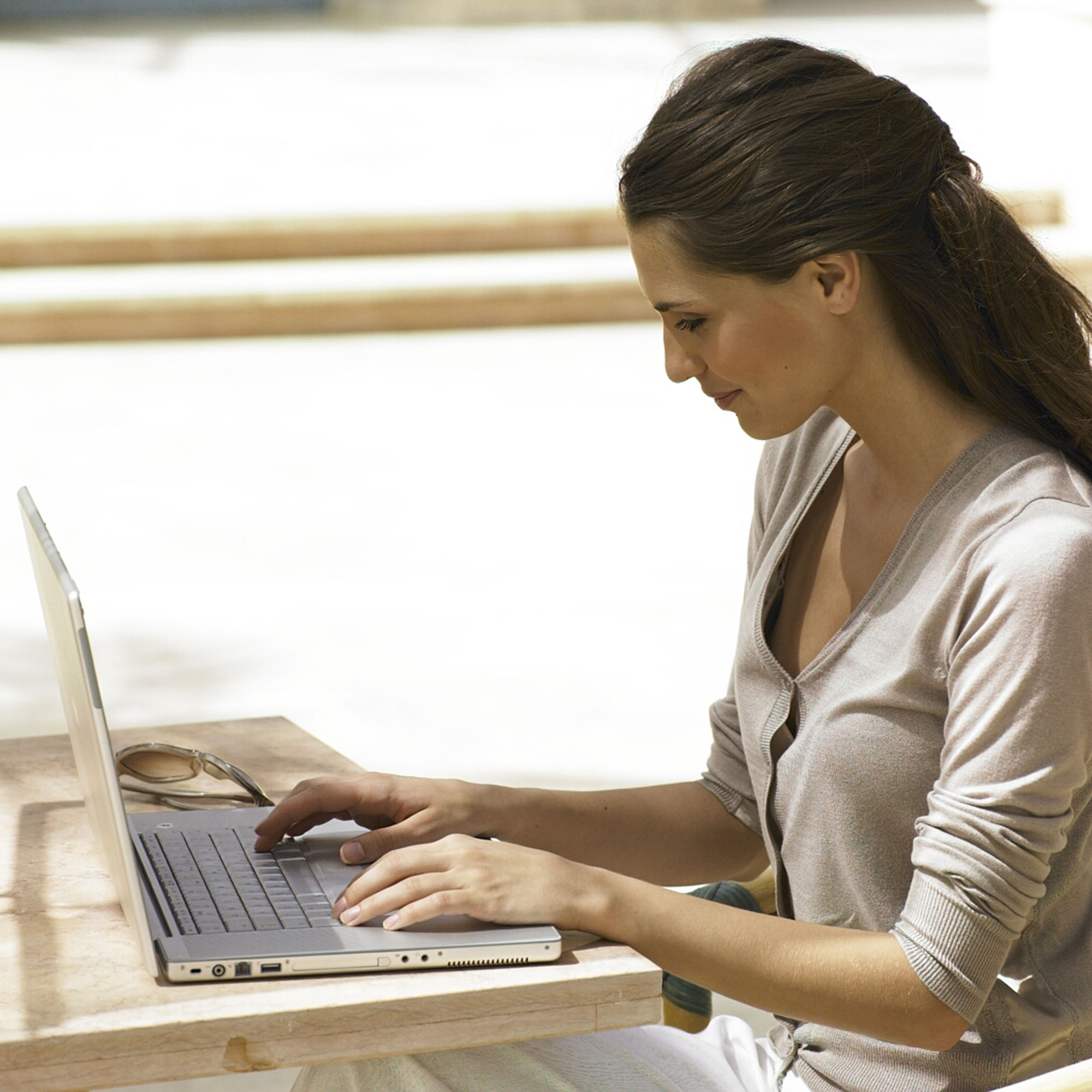 Brunette woman sitting at mac laptop computer