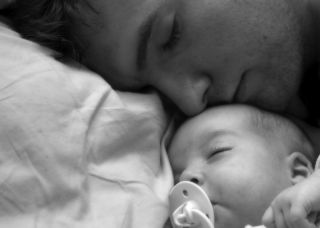 A father sleeps with his baby.