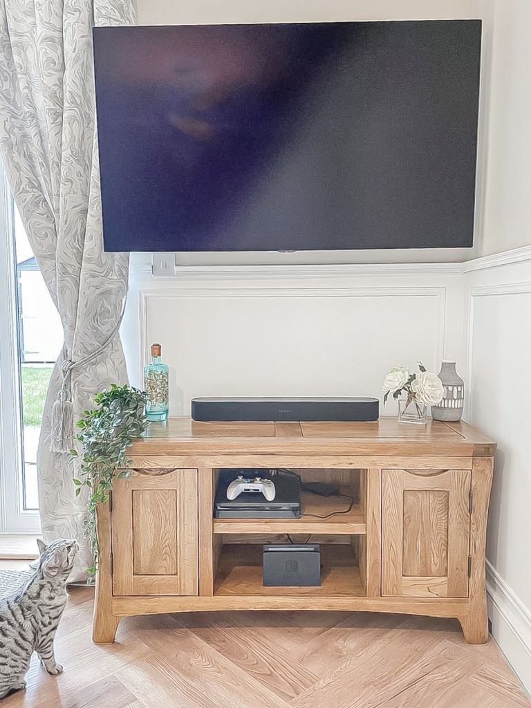 Wall mounted TV on wooden cabinet with all wires concealed
