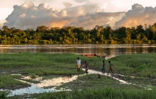 Children play on the river bank, near the village in New Guinea, Indonesia.