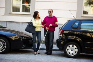 A man walks with a cane, helped by a woman.