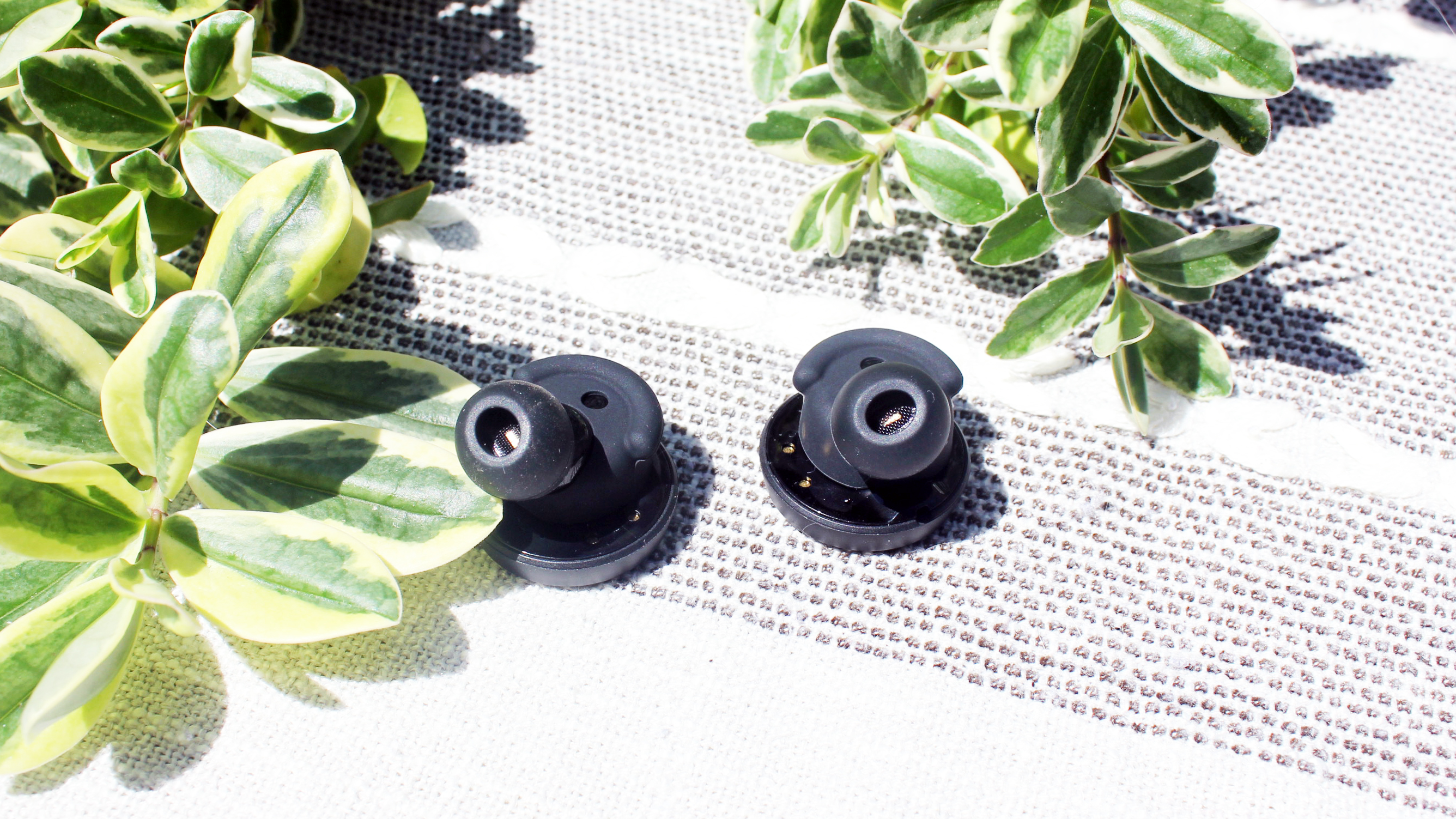 the nurtrue earbuds on a table, showing the underside of the earbuds