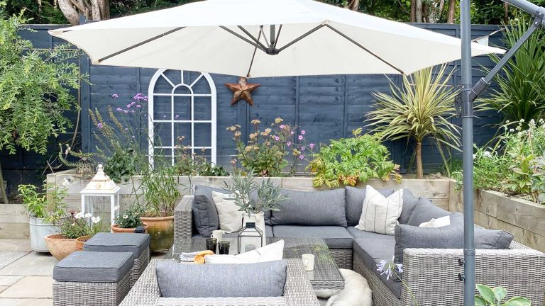 cheap landscaping ideas with painted fence parasol and patio seating from The Indigo House