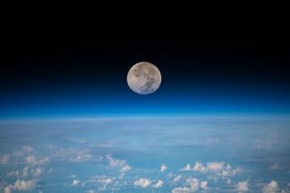 A past full moon of June, also known as the Strawberry Moon, looms above Earth's horizon in this undated photo taken by an astronaut at the International Space Station. The image was captured on June 17 as the space station was orbiting 254 miles (409 kilometers) above the Pacific Ocean northeast of Guam.