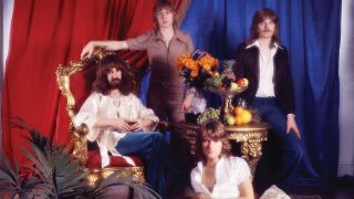 Barclay James Harvest against red and blue curtains surrounded by fruit and gilded furniture