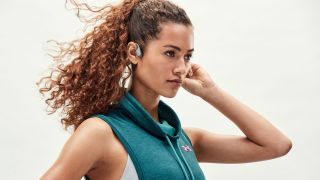 The best bone conduction headphones: A woman wearing the Aftershokz Aeropex headphones
