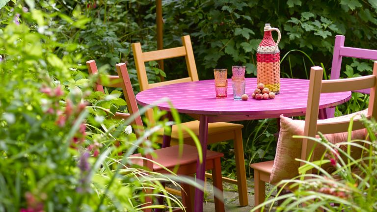 late summer garden ideas: orange and pink painted outdoor dining set