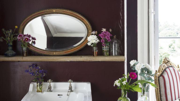 Burgundy bathroom micro trend, dark red walls above a sink basin