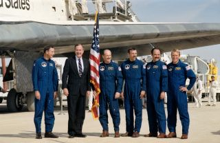 President George H.W. Bush poses with the crew of NASA's STS-26 space shuttle mission after the shuttle Discovery landed at Edwards Air Force Base in California on Oct. 3, 1988.