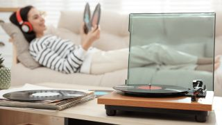 In the foreground, a sharp image of a record player can be seen. In the background, a women is lying down and looking at vinyl