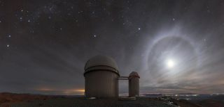 """A lunar """"halo"""" lights up the night sky above the 3.6-meter telescope at the La Silla Observatory in Chile. This phenomenon happens when the moon is at an altitude of about 22 degrees above the horizon, where light refracts through icy cirrus clouds. """"Light rays that do this tend to 'bunch up' at the angle that represents the least amount of deviation from their original path. For the particular shape of ice crystal lurking within the cirrus clouds, this minimum deviation angle happens to be around 22 degrees,"""" ESO officials said in a description."""
