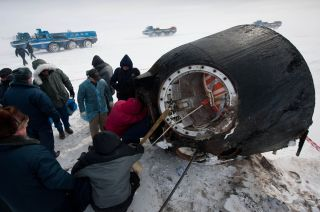 Russian support personnel work to help get crew members out of the Soyuz TMA-01M spacecraft shortly after the capsule landed with Expedition 26 Commander Scott Kelly and Flight Engineers Oleg Skripochka and Alexander Kaleri near the town of Arkalyk, Kazak