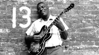 Howlin' Wolf holding a guitar and standing against a wall with 13 painted on it