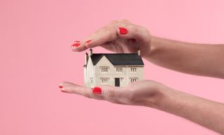 HELOC vs Home equity loan: A tiny house sitting in a person's palm in front of a pink wall