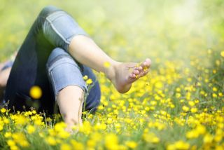 A woman lays in a field of flowers with bare feet.